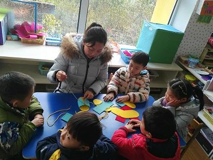 老师认真的教小朋友系鞋带的技能,让小朋友的事情自己完成,养成爱