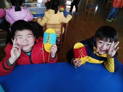 区域游戏:小朋友学习系鞋带